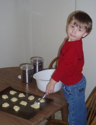 my son spooning batter onto cookie sheet