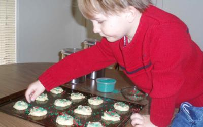 my son decorating the cookies with sprinkles
